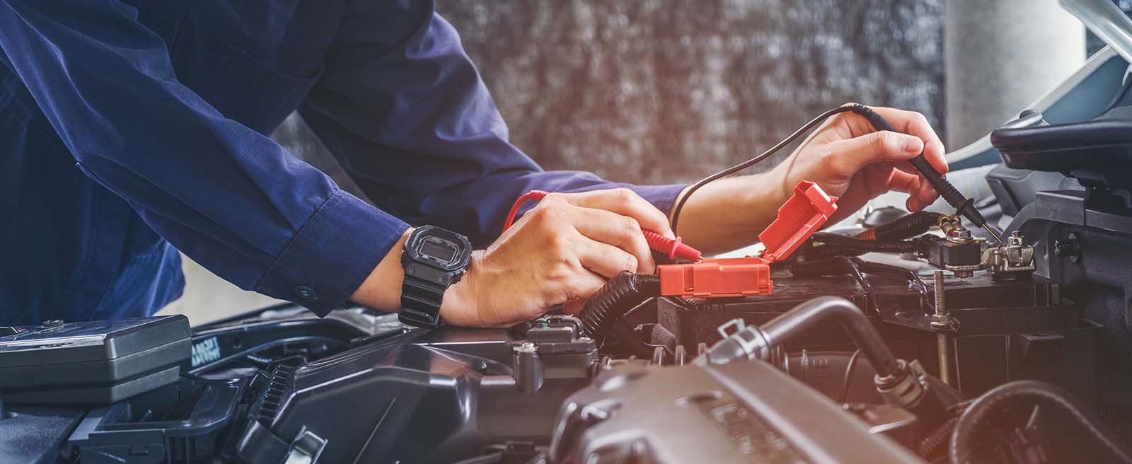 Auto technician working on battery